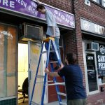 Members working to remove the old store front signage.